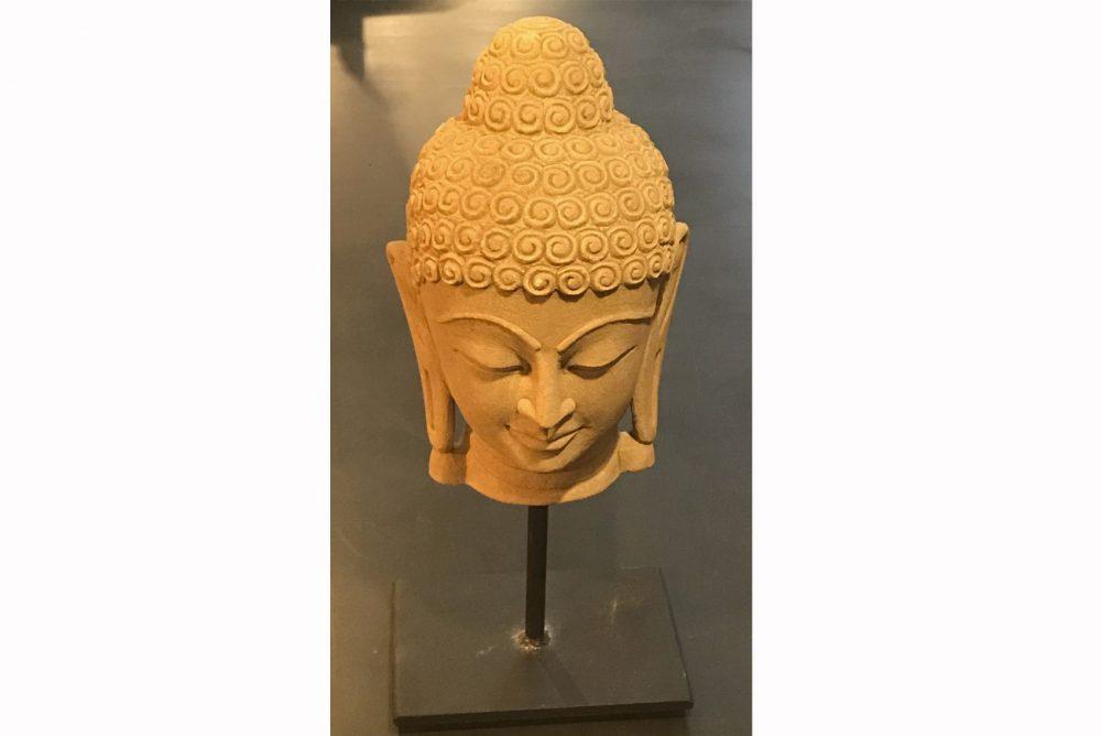 la tête de bouddha décorative posé sur un socle